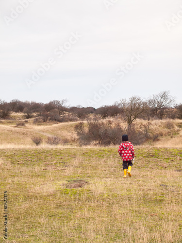 small boy walking alone in a dunes in winter