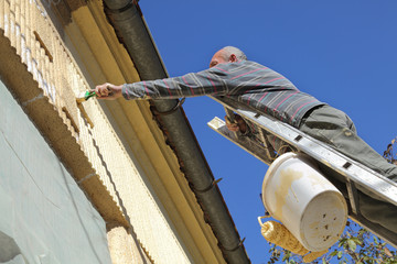 Renovation, senior worker at ladder painting old house facade