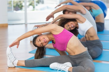 Sporty people doing stretching exercises in fitness studio