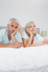 Displeased mature man and woman lying in bed