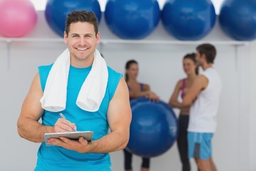 Male trainer holding clipboard with fitness class in background