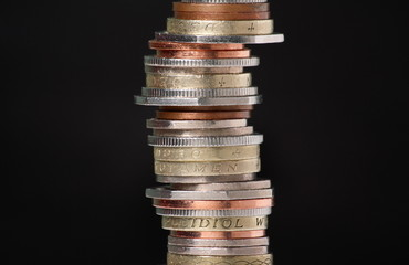 Stack of British Coins on black with copy space
