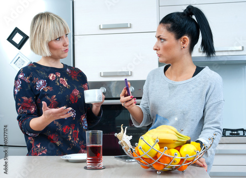 two attractive woman friends drinking coffee and talking