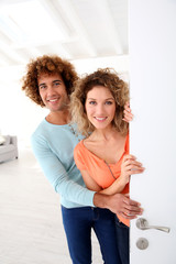 Cheerful couple opening new home entrance door