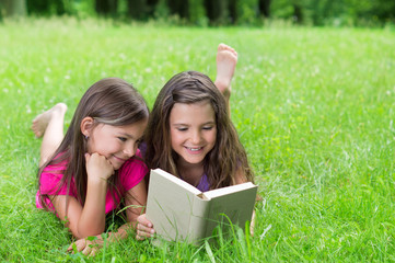 Zwei Mädchen auf saftiger Wiese beim lesen