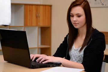Schuelerin schreibt am Laptop