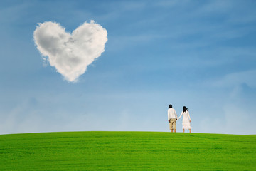 Couple at green hill under heart shape cloud