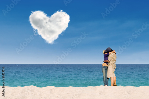 Couple kissing under love cloud at beach