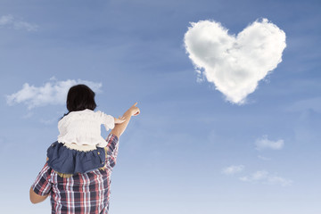 Girl on dad's back pointing at heart cloud