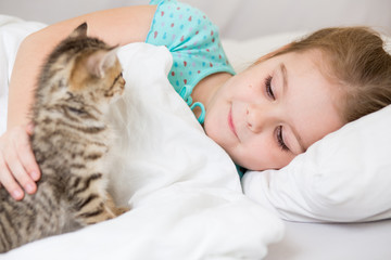 Kid girl with kitten laying in the bed