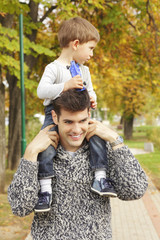Cute little boy riding piggyback with his dad