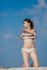 Slim girl undressing against of sky looking away