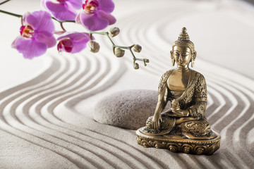 Buddha in zen flower garden with smooth grooves in sand