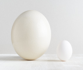 Ostrich egg and chicken egg on white table