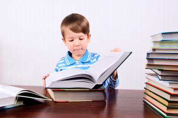 little boy opens a large book and looking into it