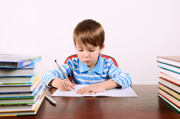 boy writes in exercise book