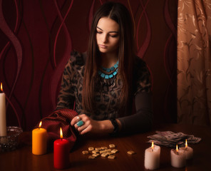 Young woman with runes and divination cards in room