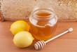 Fresh honey in a glass jar and lemons.