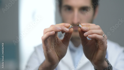 Young friendly doctor breaking a cigarette, quitting smoking con