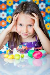 Cute little girl painting Easter eggs