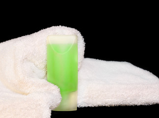 Fluffy white bath towel,body wash gel bottle,isolated on black