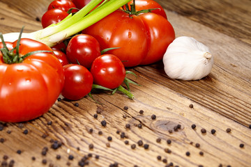 Red tomatoes with pepper and garlic on old wooden table