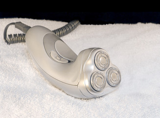 Man's silver color electric razor, cord, and white towel