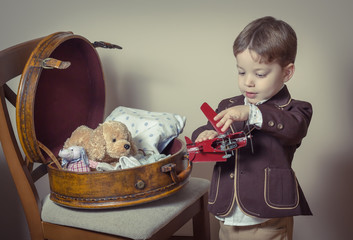 Vintage portrait of boy playing with tin toys