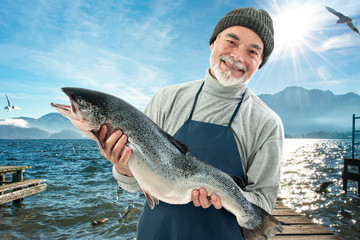 Fisher holding a big atlantic salmon fish