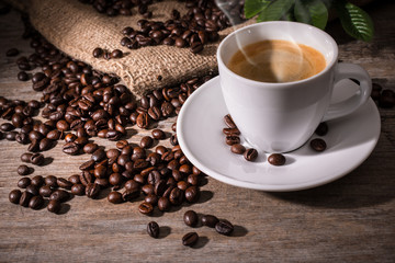 Cup of coffee and coffee beans on wooden background © Alexander Raths