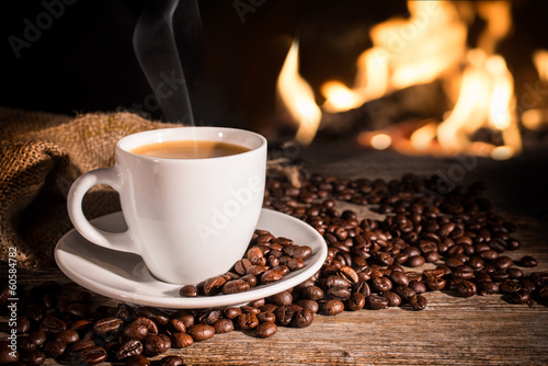 Keuken foto achterwand Cafe Cup of hot coffee and coffee beans near fireplace