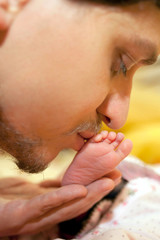 Father and baby. Man kissing newborn foot