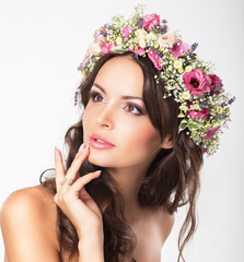 Young Beauty. Woman's Face with Bouquet of Natural Flowers