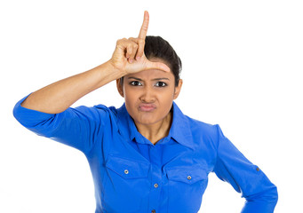 Funny young woman displaying loser sign on her forehead