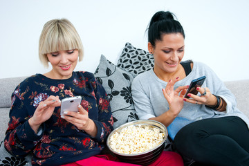 two attractive woman friends with mobile phone and popcorn