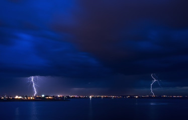 Spears - powerful lightning strikes over a lake in the city