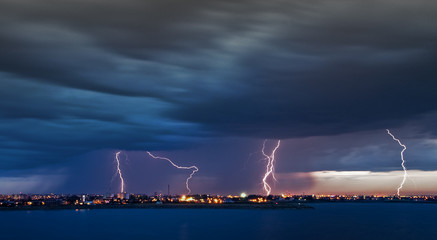 5 Apostles - powerful lightning strikes over a lake in the city