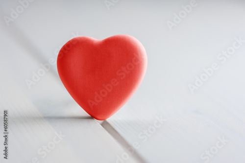 Red valentine heart on white wooden table
