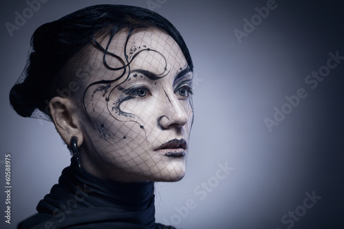 portrait of young gothic woman isolated on dark background with