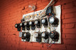old electric meters on a red brick wall - 60591144