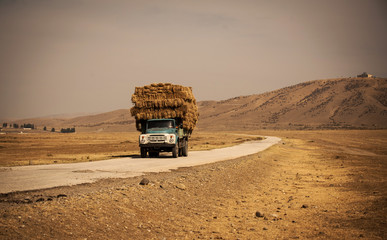 truck with straw on the road