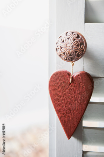 Red wooden heart hanging on the white terrace window