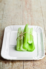 fresh green celery stems in plate