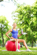 Blond female athlete sitting on pilates ball and holding a bottl