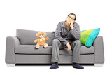 Young man in pajamas in thoughts seated on sofa with teddy bear