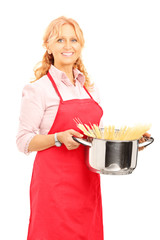 Mature woman holding cooking pot with spaghetti