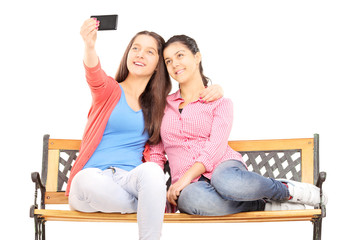 Two young girls seated on bench taking picture of themselves wit