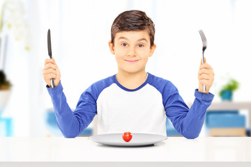 Young boy holding fork and knife with tomato on plate in front o