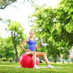 Young female athlete sitting on pilates ball holding a bottle in