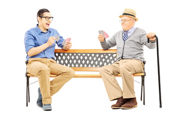 Young man and senior gentleman playing cards seated on a bench